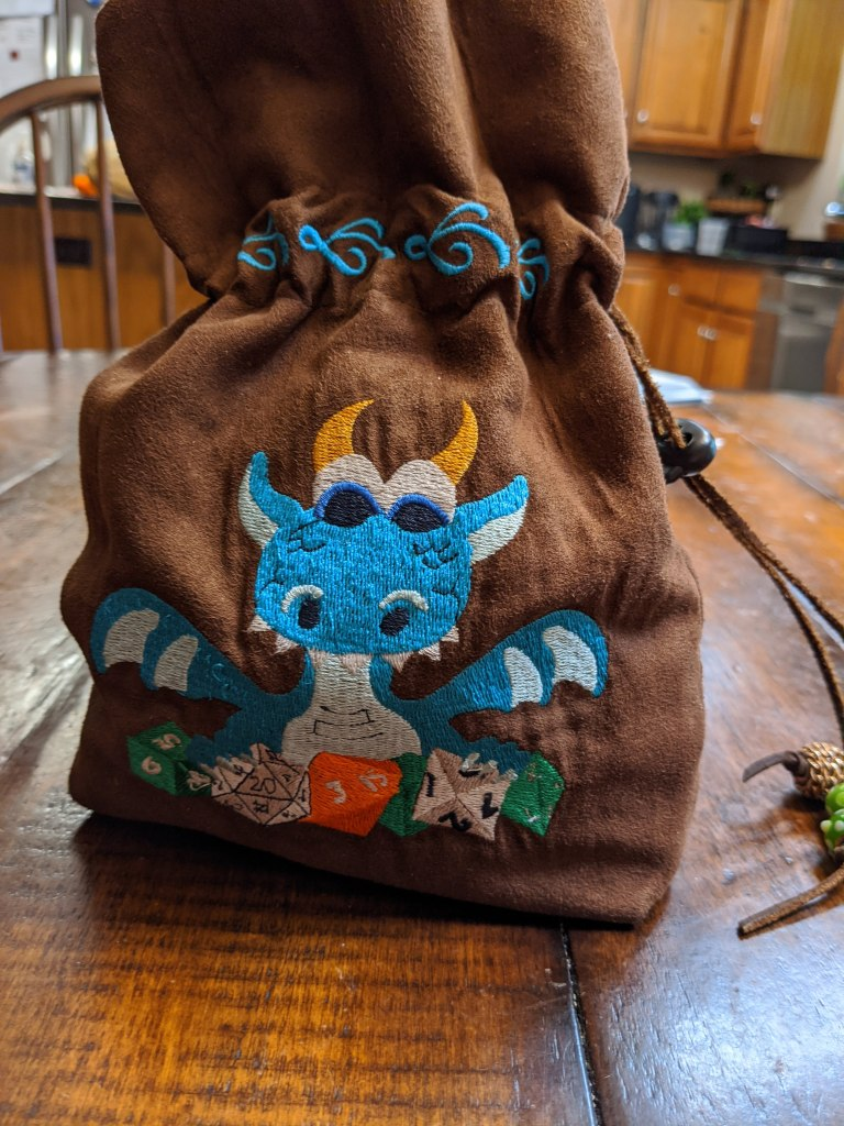 Image of a brown dice bag with a blue embroidered dragon with gold horns happily holding onto its green, white, and orange role playing dice.
