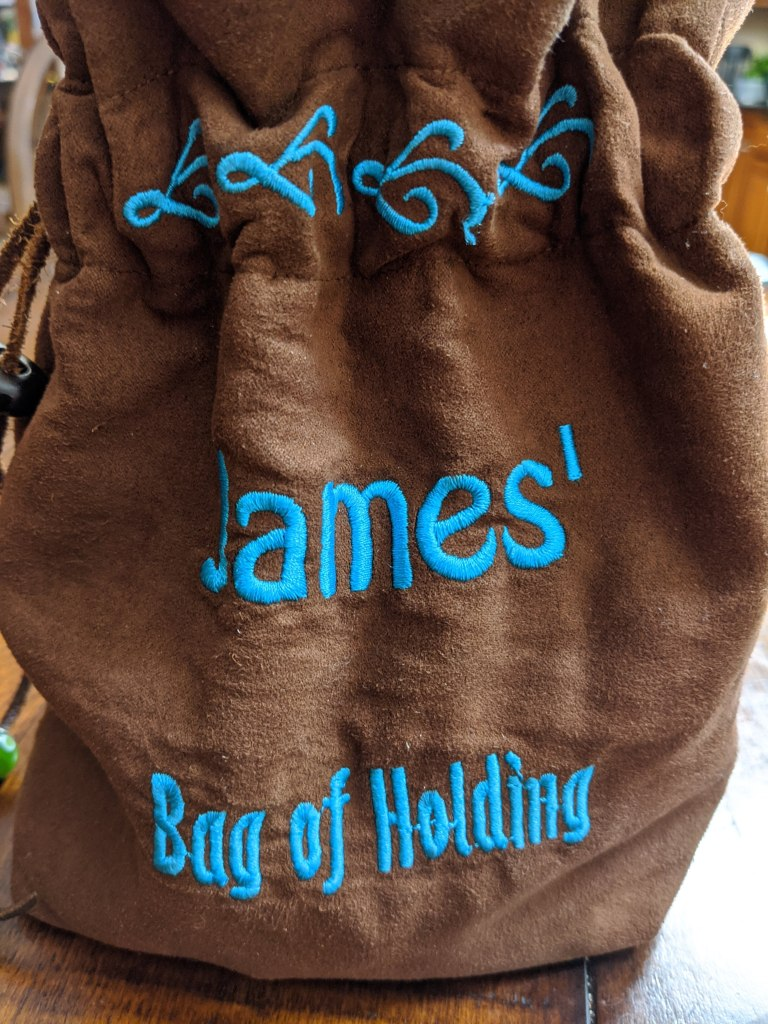 """Reverse side of the blue dice bag with the words """"James' bag of holding"""" embroidered on it."""