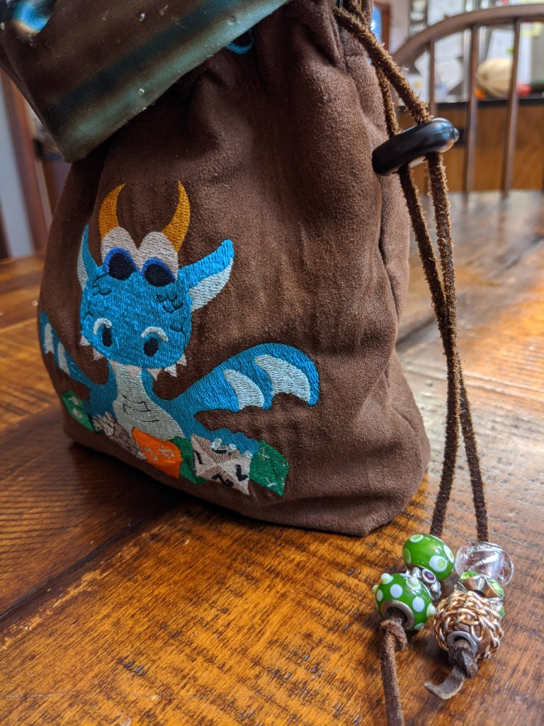 Side view of the blue dragon dice bag, showing the leather strap that cinches the bag closed, embellished with green and clear beads.
