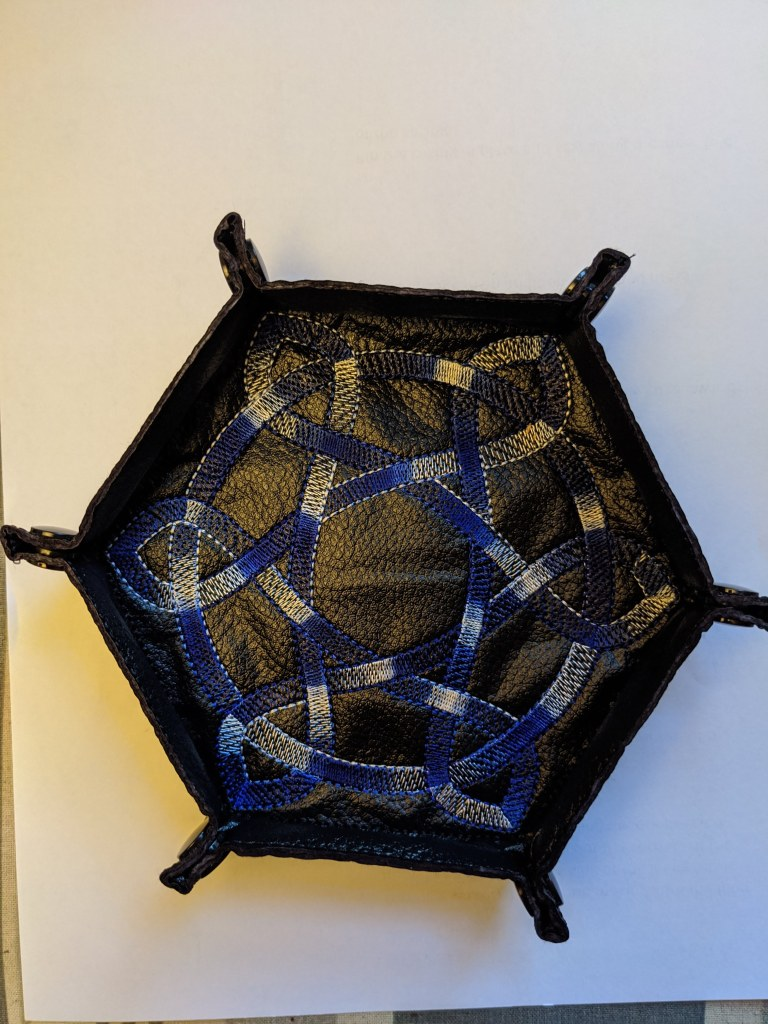 Soft sided dice tray shown in black vinyl with a varigated blue celtic knot embroidered on it.