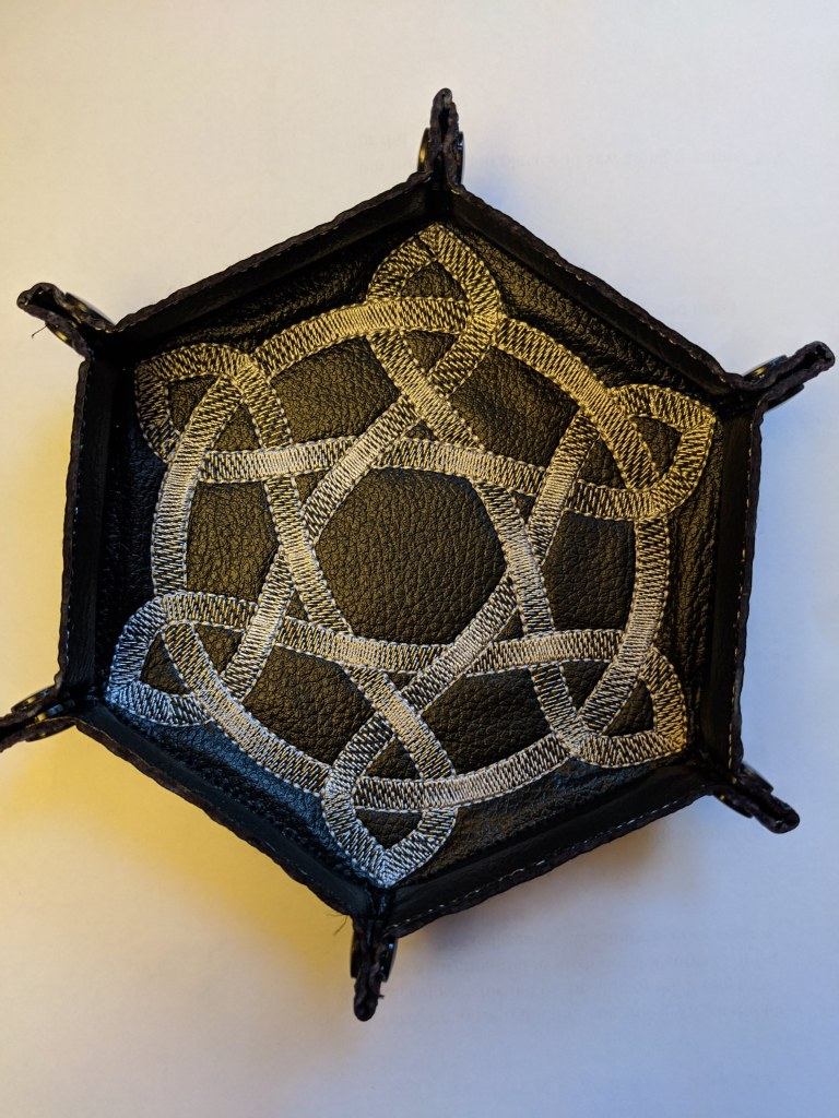 Soft sided dice tray shown in black vinyl with a silver metallic celtic knot embroidered on it.
