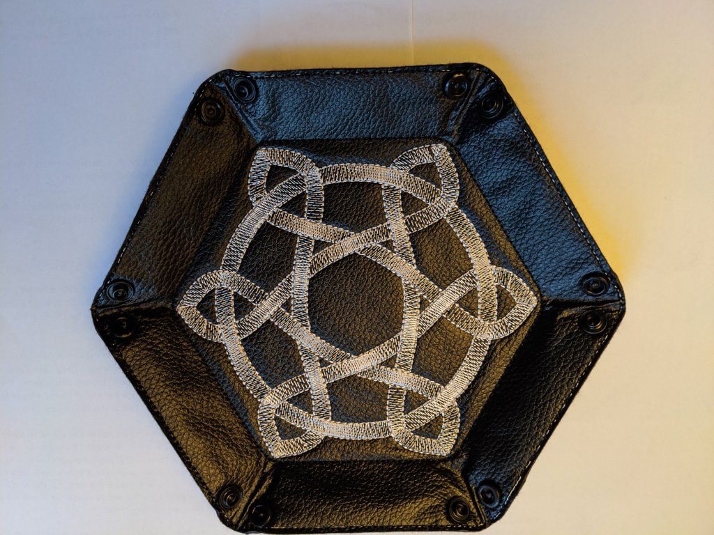 Soft sided dice tray shown in black vinyl with a silver metallic celtic knot embroidered on it, unsnapped and laying flat.