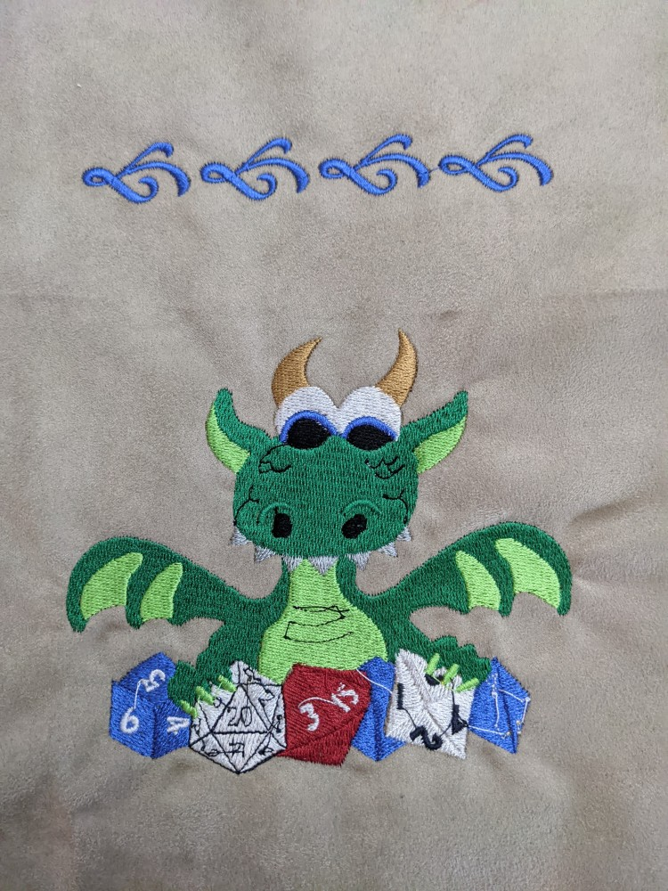 Image is of an embroidered green dragon happily holding onto it's blue, white, and red multi-sided dice.