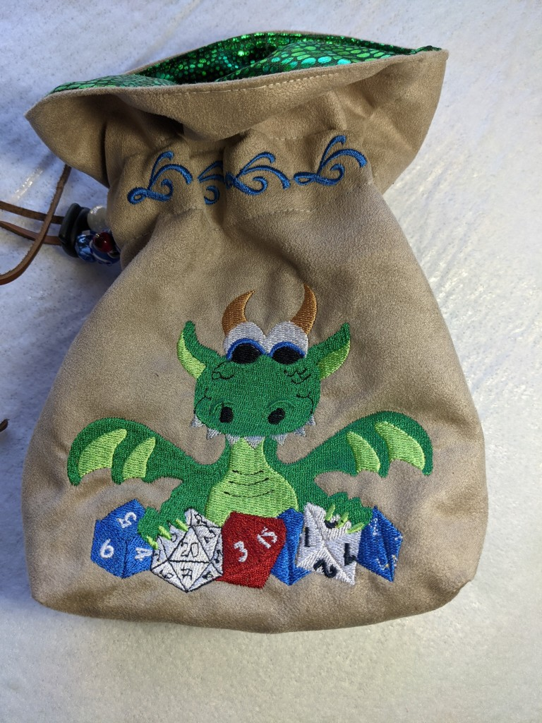 Light tan dice bag with a green embroidered dragon with gold horns happily holding onto its blue, white, and red role playing dice.