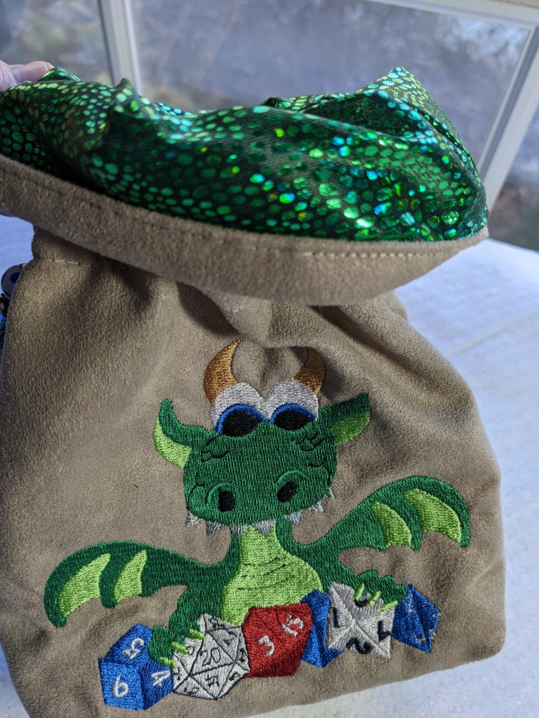 View of the tan dice bag showing a sparkly green lining fabric on the inside.